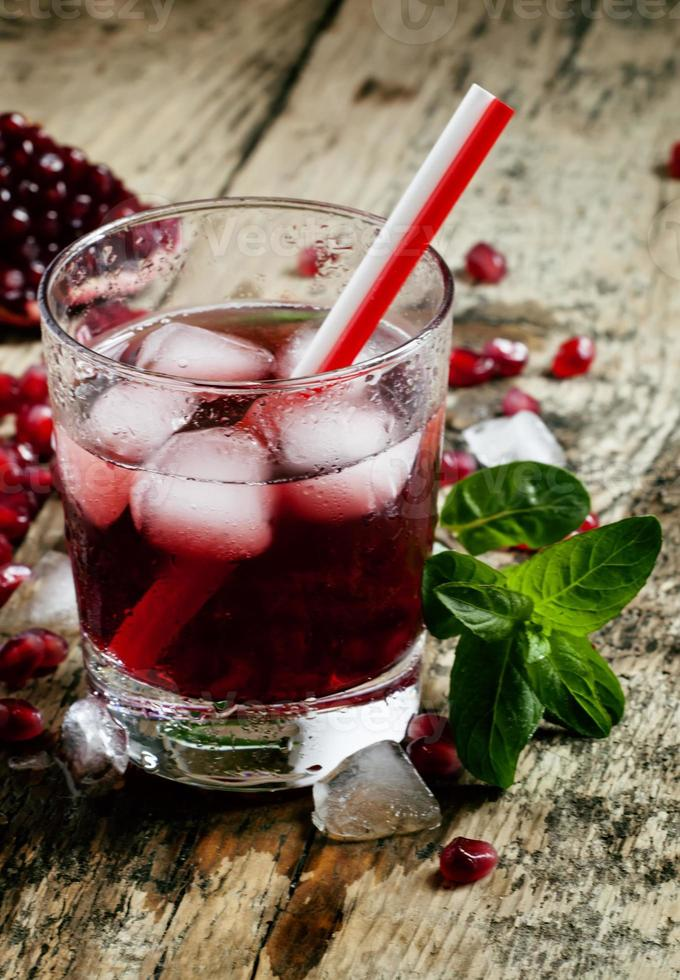 Fresh red juice cocktail with pomegranate seeds, mint and ice photo