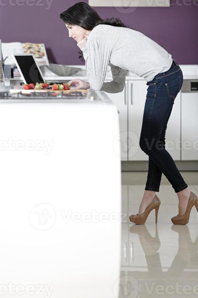 mujer en la cocina leyendo la receta foto