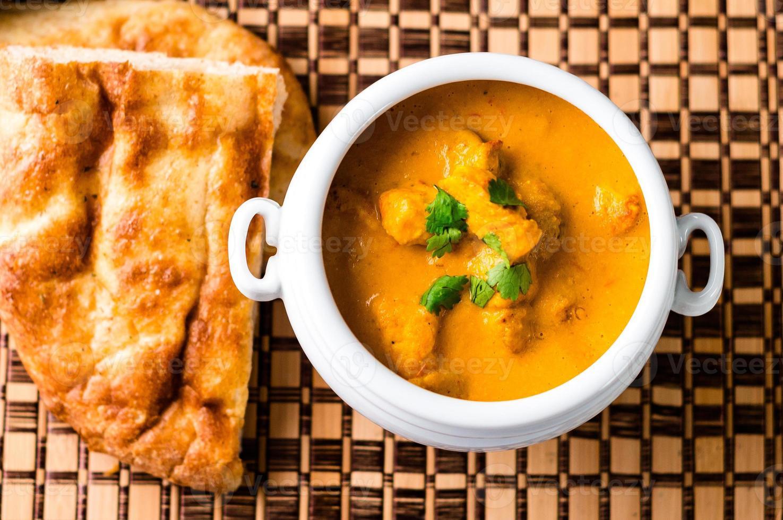 Plato de pollo al curry con mantequilla india y pan naan foto