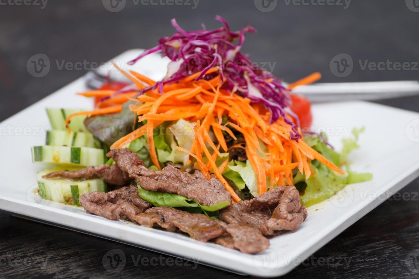 Ensalada asiática de carne de res en rodajas con repollo rojo y zanahorias foto