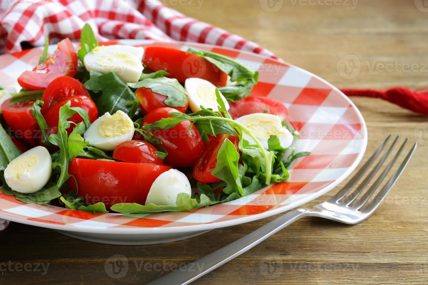 salad with fresh tomatoes, arugula and quail eggs photo