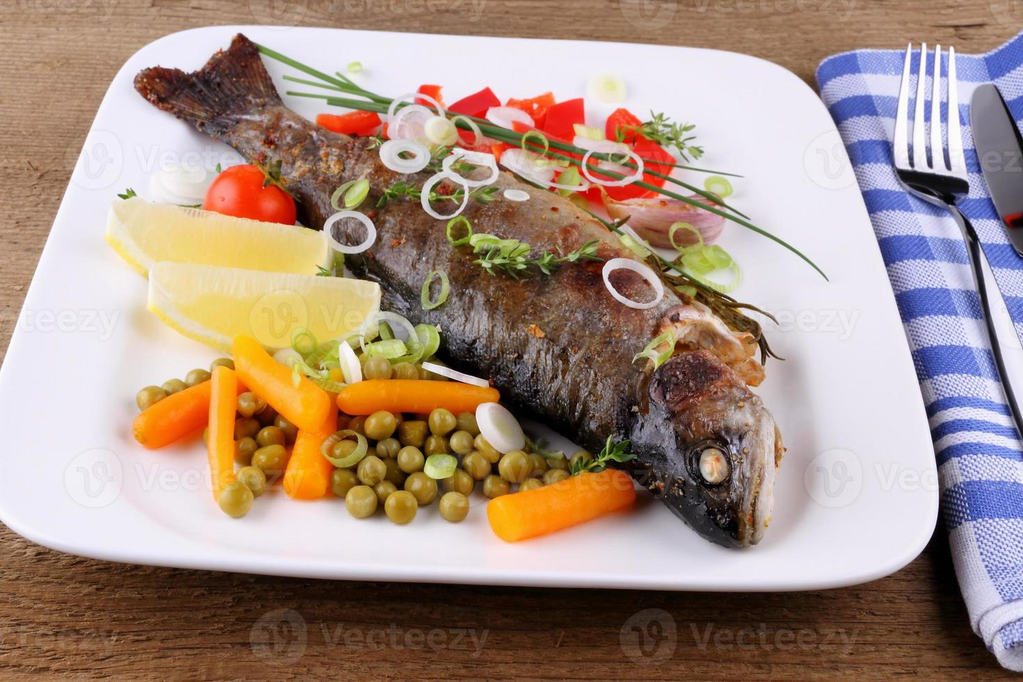 Grilled trout and quite different vegetables with cutlery photo