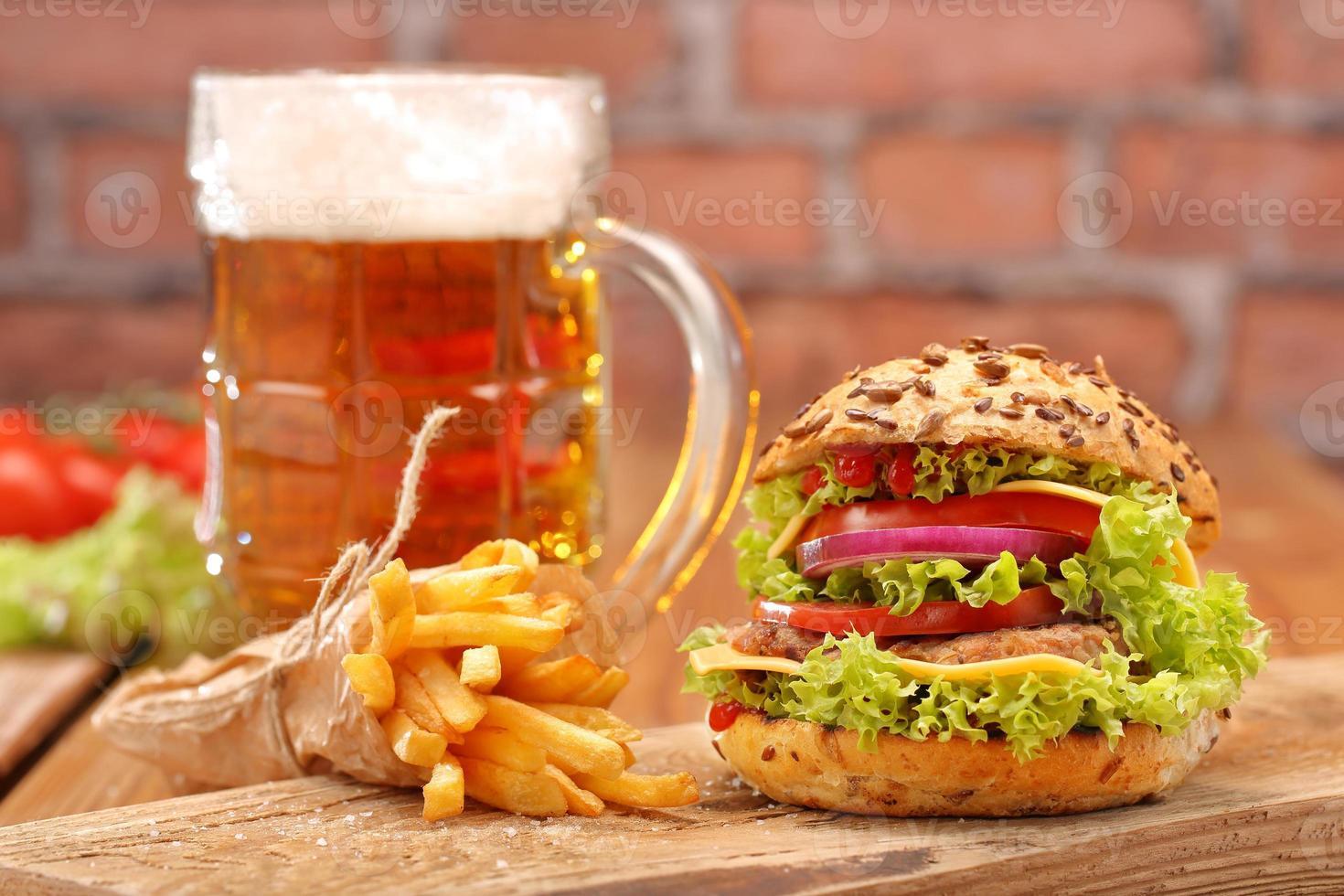 Hamburguesa a la parrilla con papas fritas y cerveza sobre fondo de pared de ladrillo foto