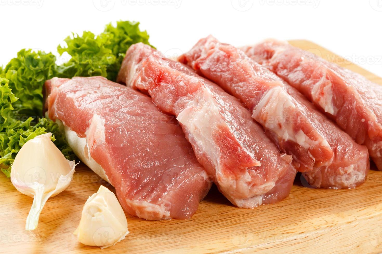 carne de cerdo cruda fresca en tabla de cortar foto
