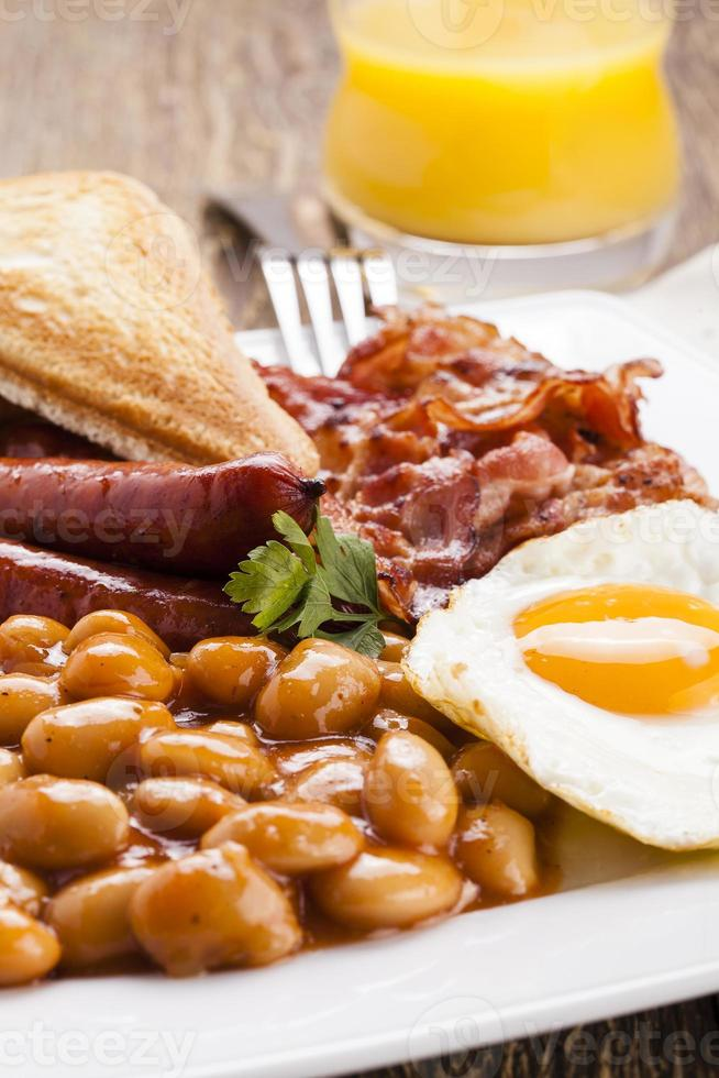 Full english breakfast with bacon, sausage, fried egg, baked bea photo