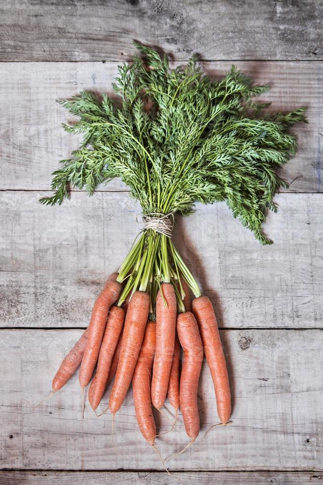 Fresh carrots on grungy wooden background photo