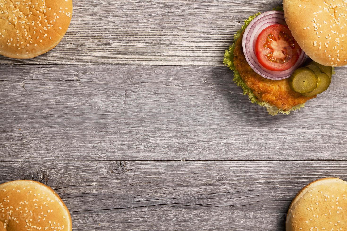 hamburguesa casera de pollo con lechuga, tomate y cebolla foto