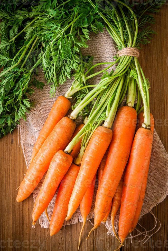 fresh organic carrots bunch on wooden background photo