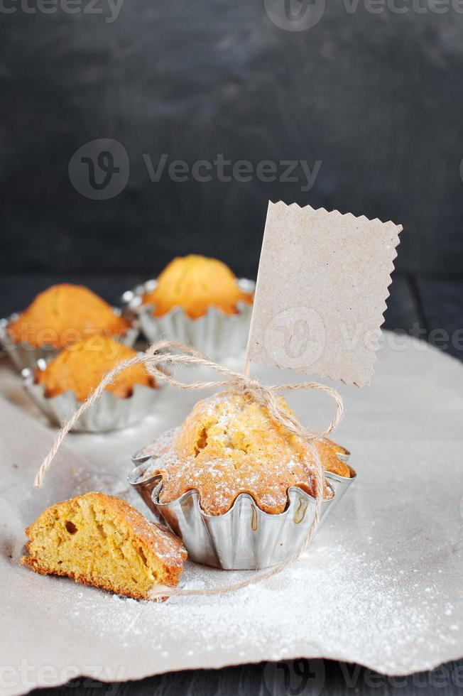 Cupcakes con etiqueta vacía en la mesa de madera foto