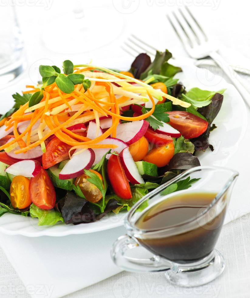 Garden salad with dressing and veggies photo