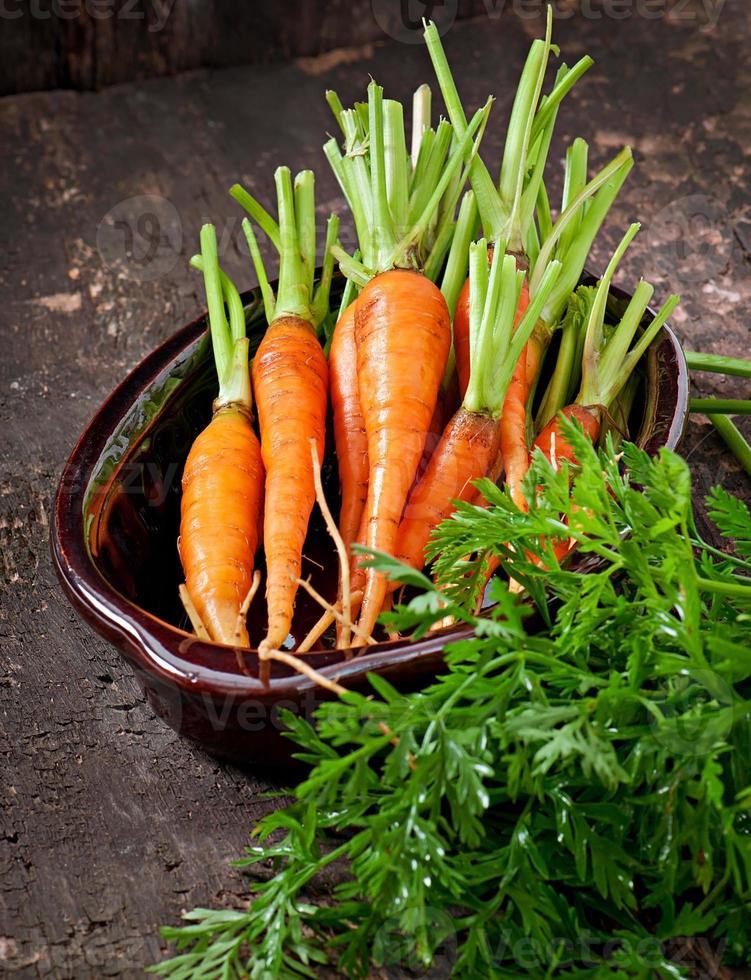 Fresh carrots on old wooden background photo