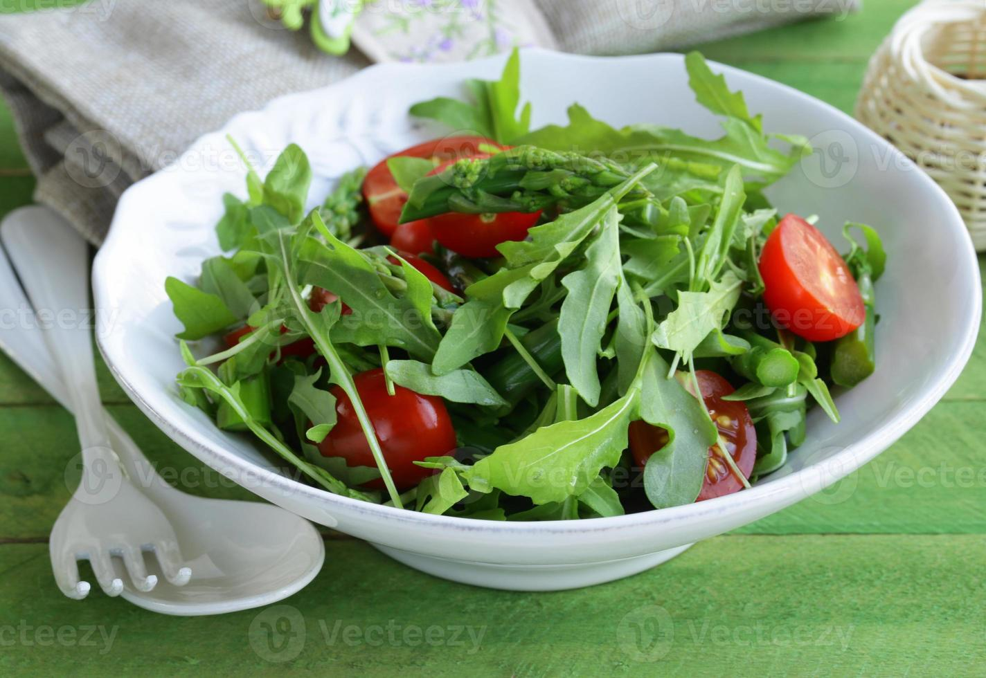 salad with arugula and tomatoes served on a wooden table photo