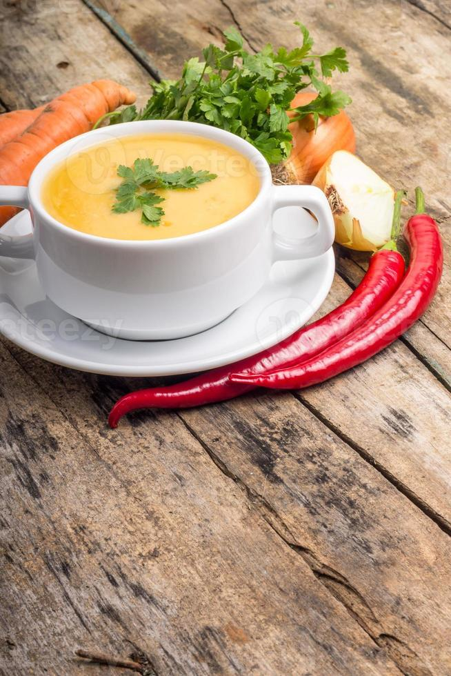 Organic food. Pea soup with vegetables around on wood background photo