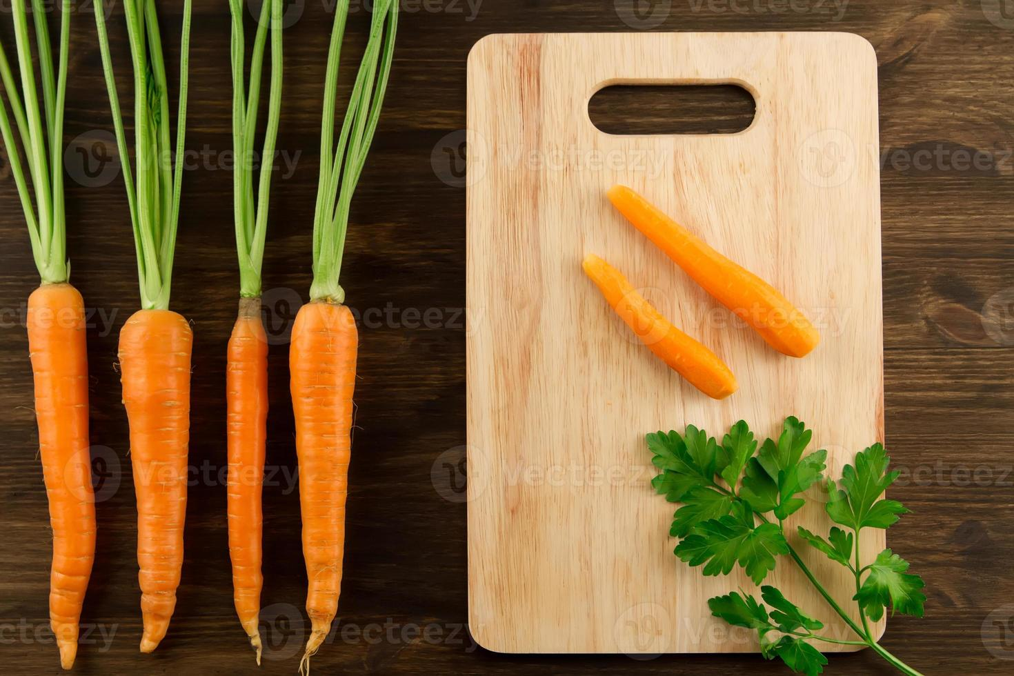 Bunch of fresh carrots with green leaves on wooden photo