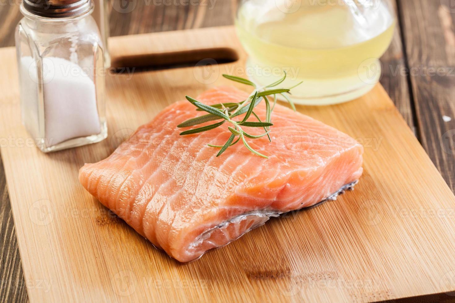Raw salmon filet on wooden cutting board photo