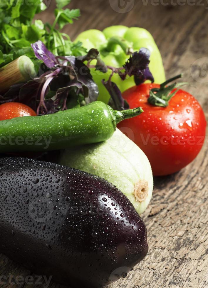 Fresh eggplant, tomatoes, peppers, zucchini, garlic and herbs photo
