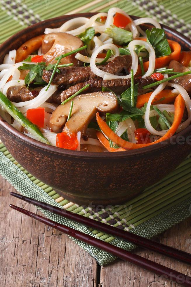 Rice noodles with meat, mushrooms and vegetables vertical photo