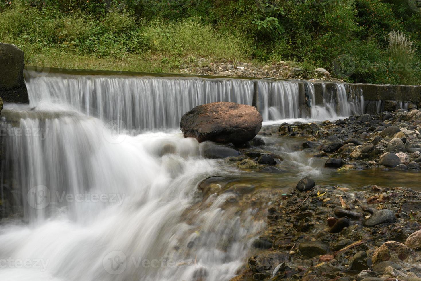 Pretty waterfall on rock stones photo