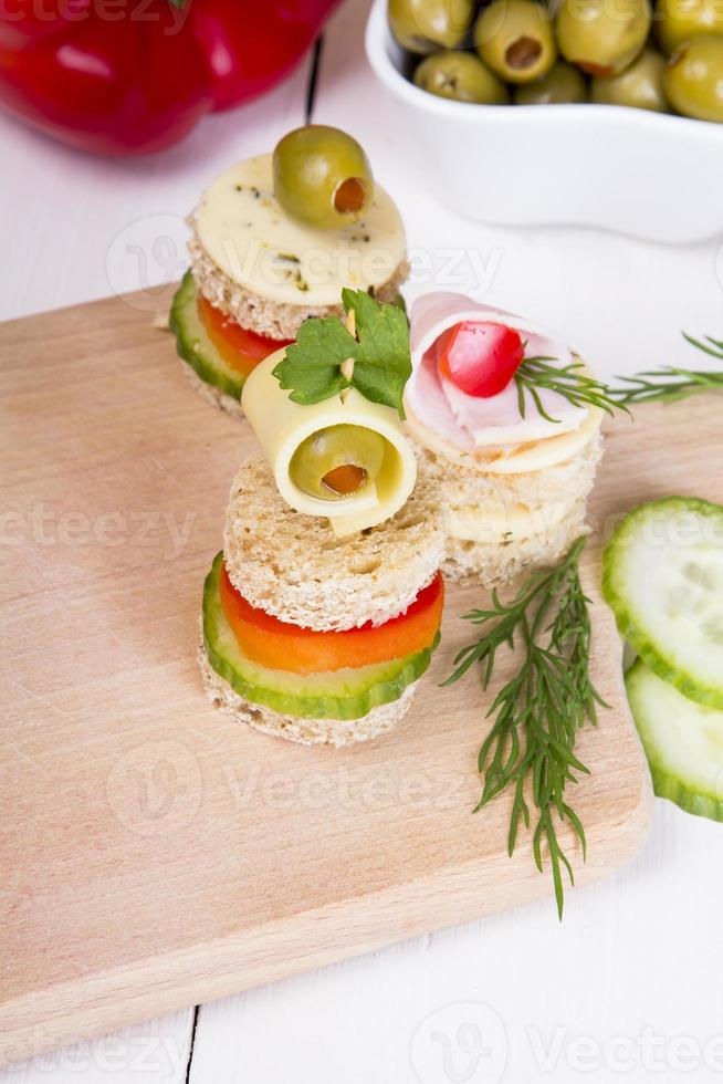 finger foods: bread, peppers, cucumber, cheese and olives photo