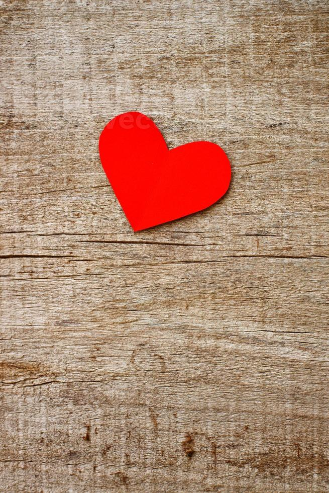 Red paper heart on grunge wooden background photo