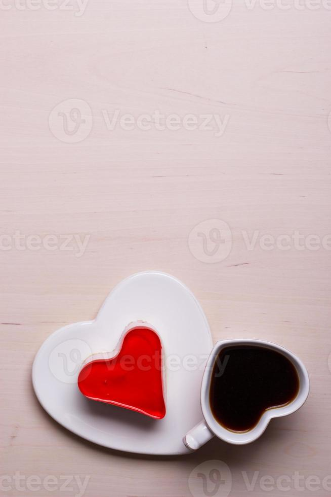 Heart shaped coffee cup and cake on wood surface photo