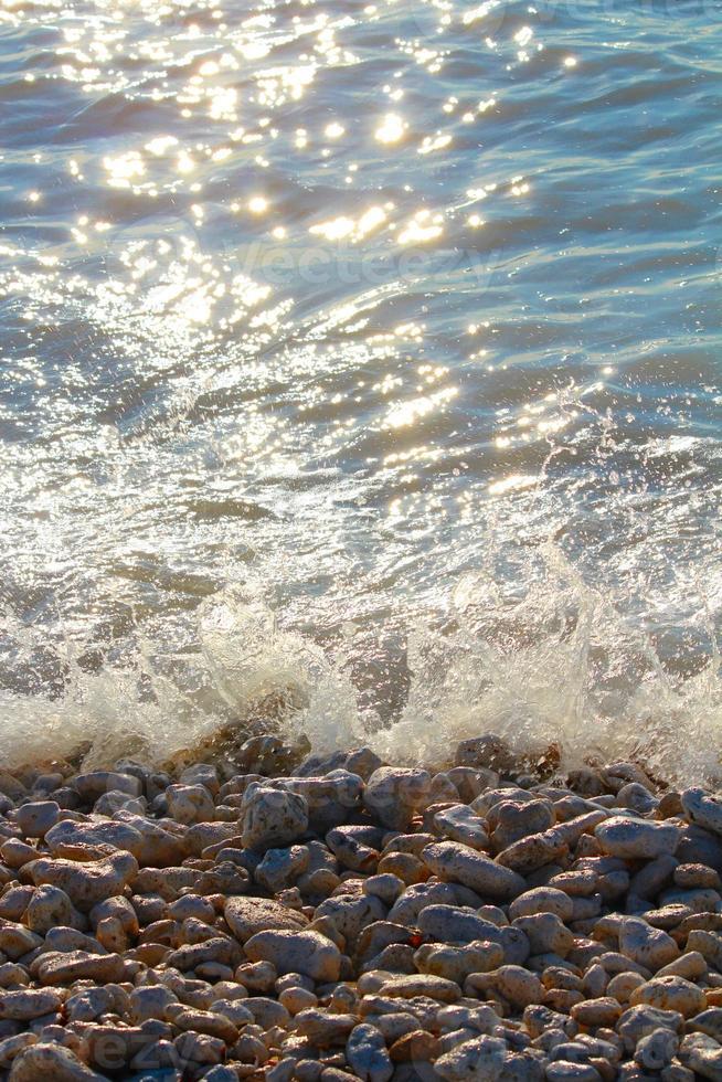 Blue ocean waves on rocky beach photo