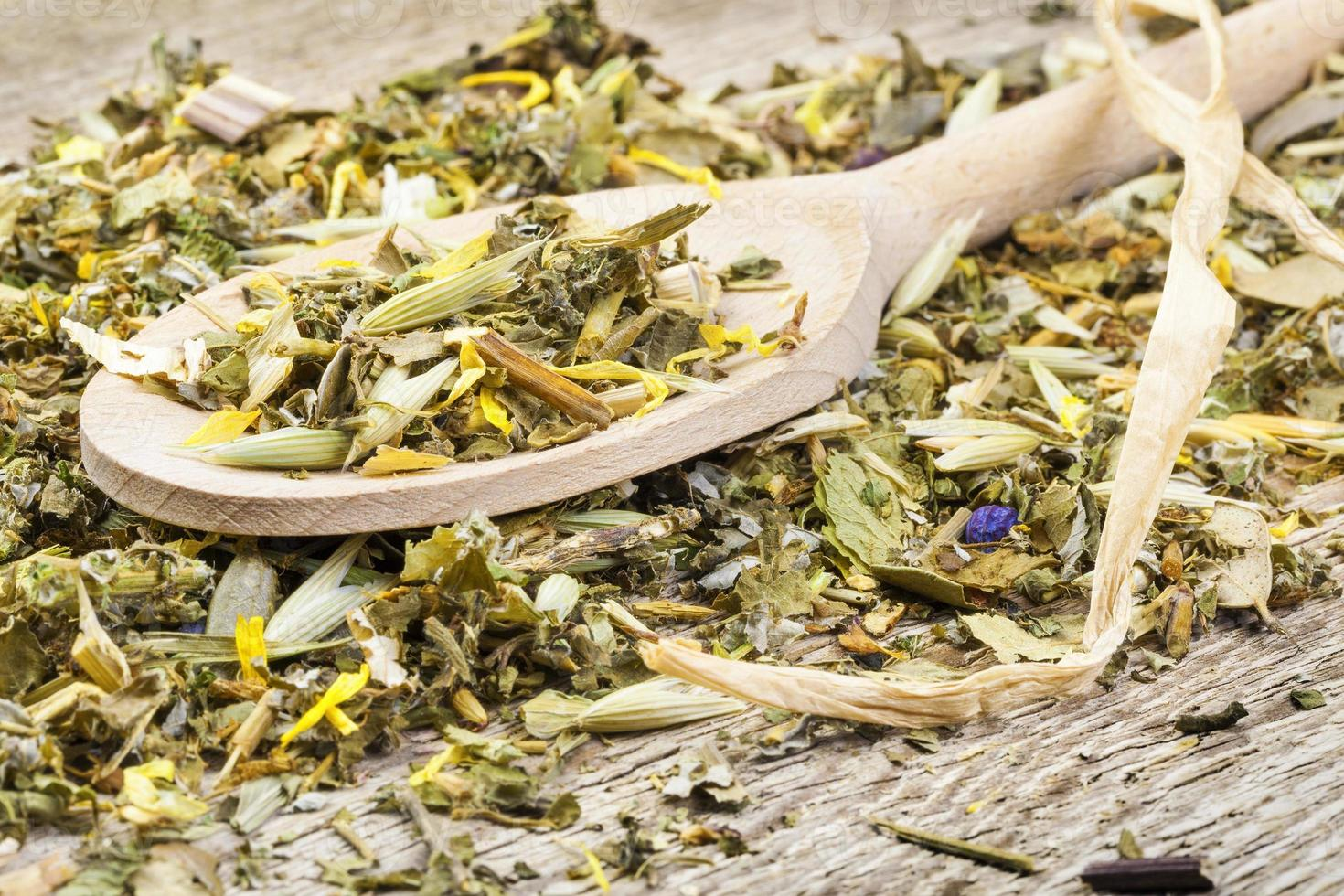 Curative natural herbal tea on wooden spoon on old table photo