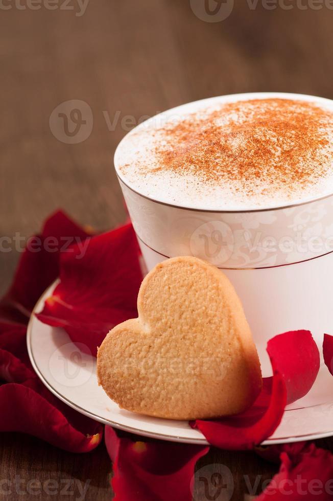 Closeup imagen encantadora forma de corazón galleta y taza de café foto