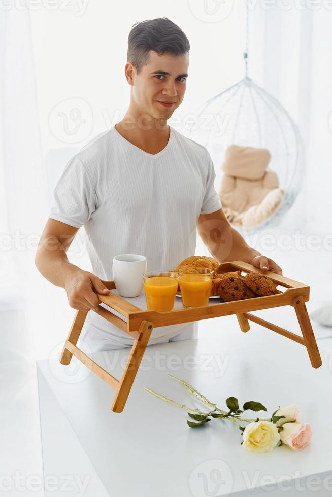 Portrait of man holding tray with breakfast photo