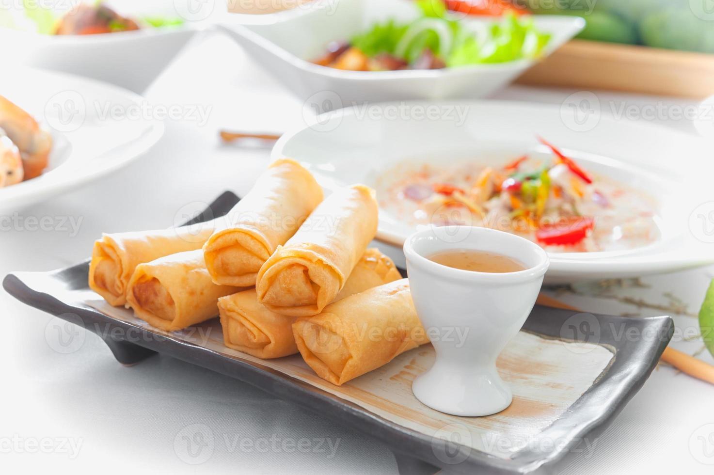 deliciosos rollitos de primavera tailandeses con salsa en el plato foto