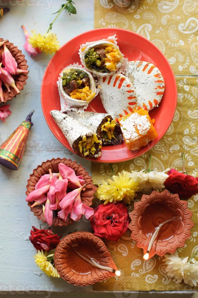 Diwali Sweets with Diyas in background photo