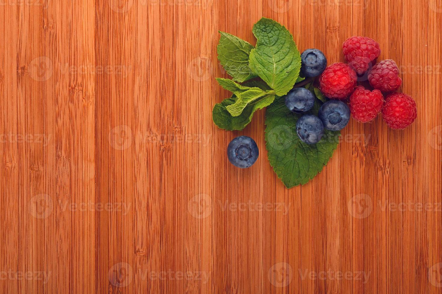 Cutting board with blueberries, raspberries and mint leaves photo