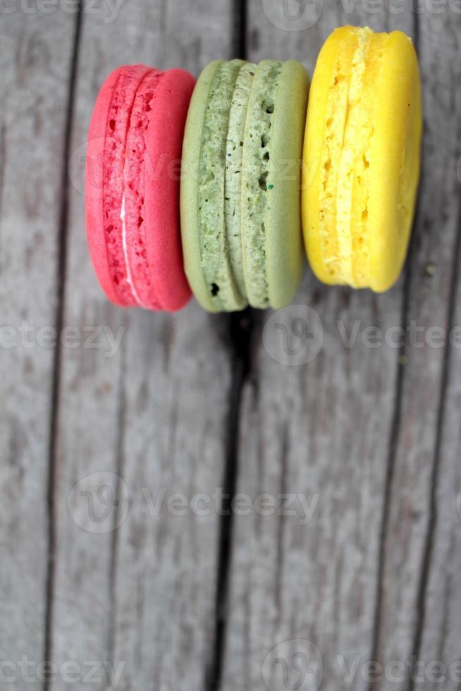 macarrones coloridos deliciosos sobre fondo de madera. foto