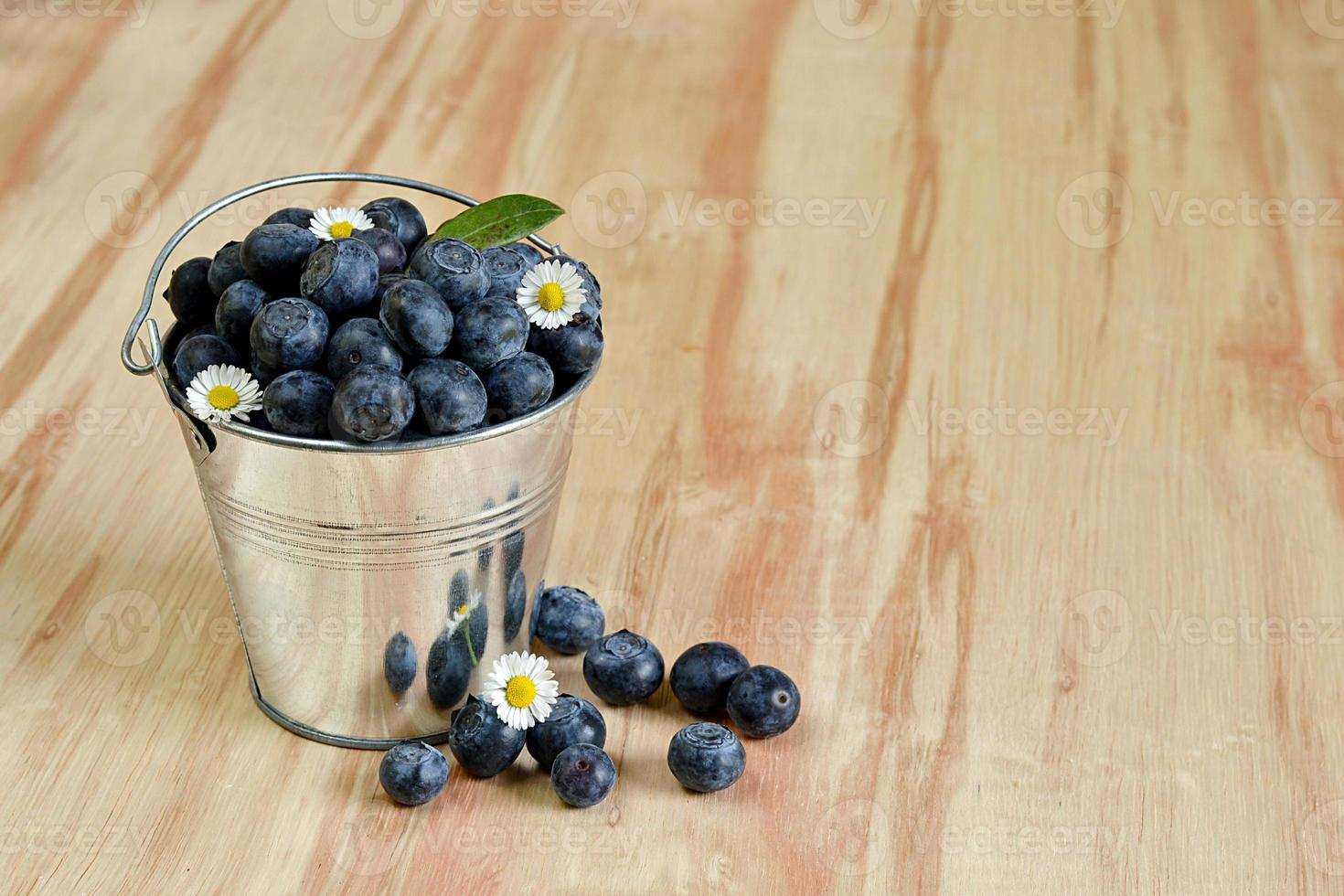 Blueberries in a bucket with daisy flowers photo