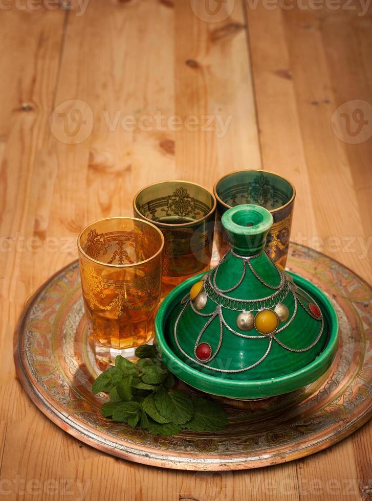 tagine y té marroquí con menta en una bandeja de metal foto