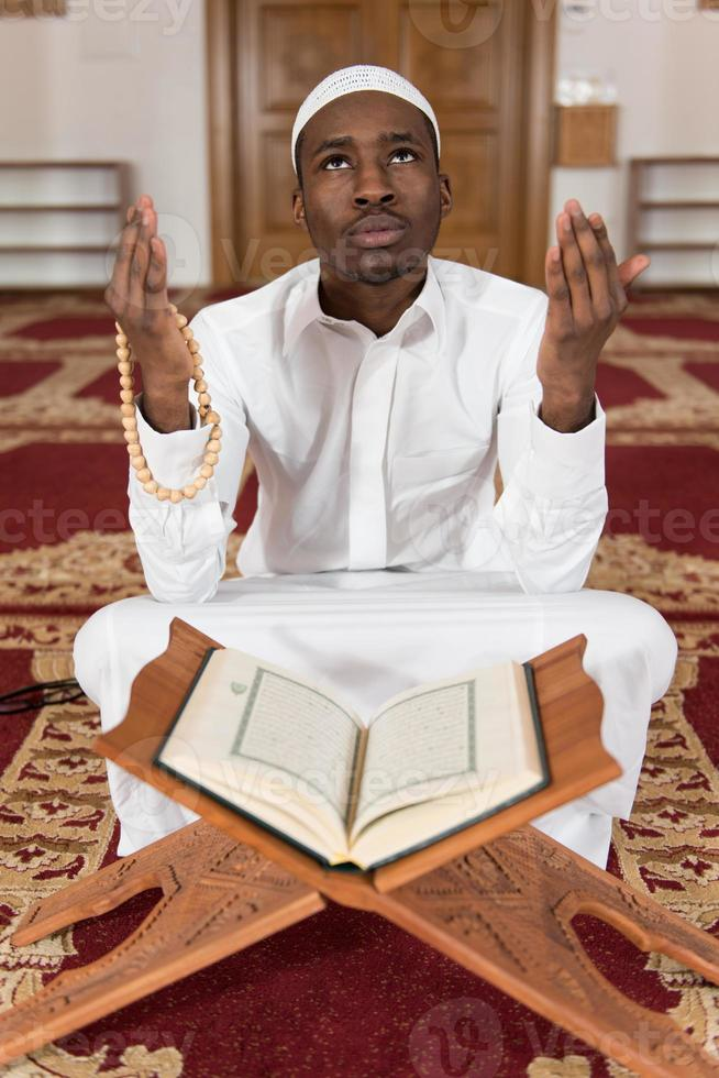 Young African Muslim Guy Reading The Koran photo