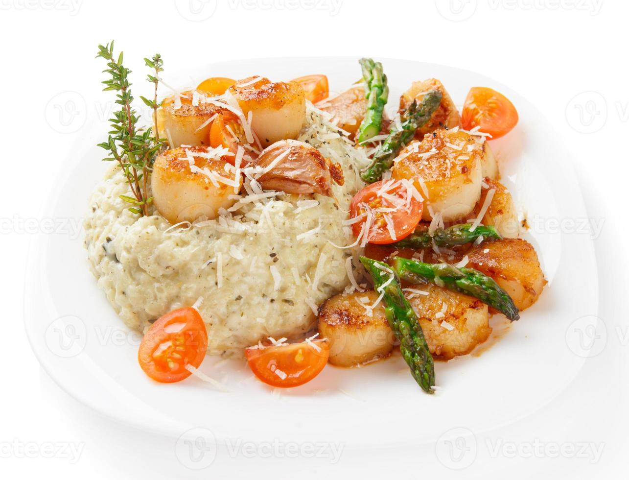Risotto with pan seared sea scallops isolated on white photo
