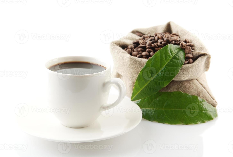 saco lleno de granos de café con hojas verdes taza de café foto