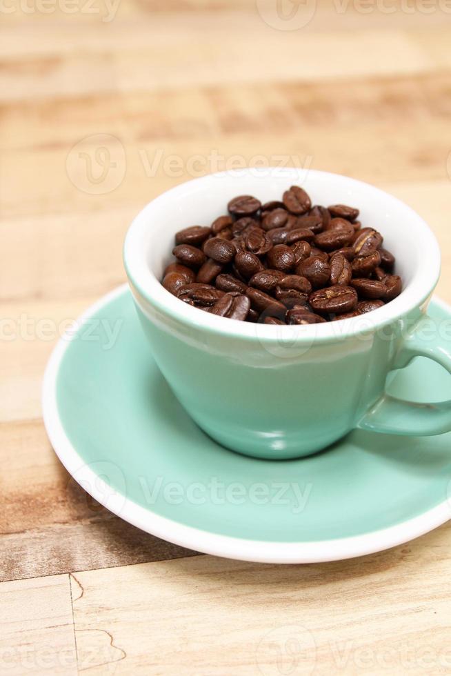 granos de café en taza verde foto
