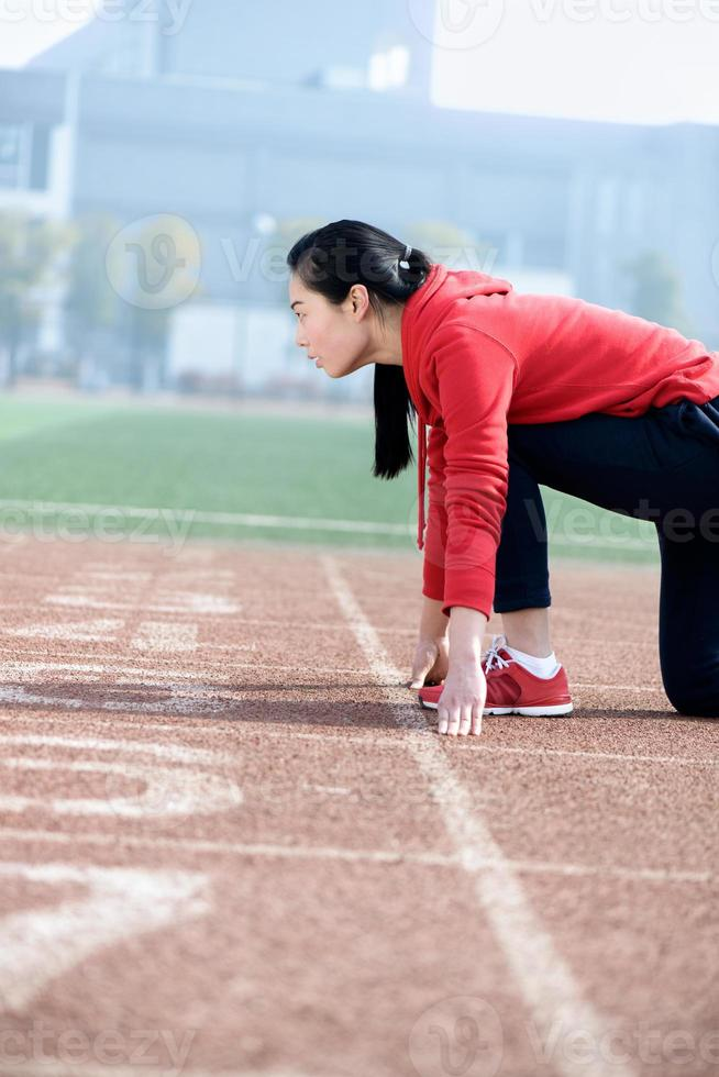 Athletic Chinese woman in start position on track photo