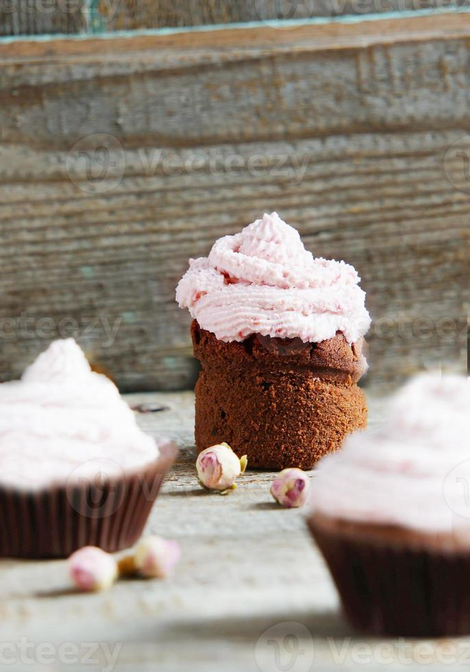 Cupcakes with cream cheese cream with raspberry and dry roses photo