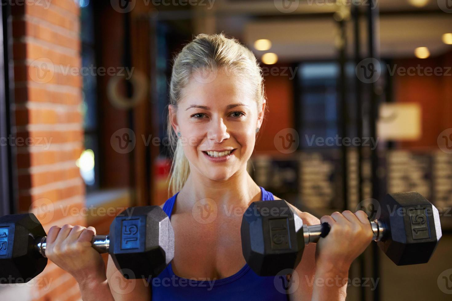 mujer en gimnasio levantando pesas de mano foto