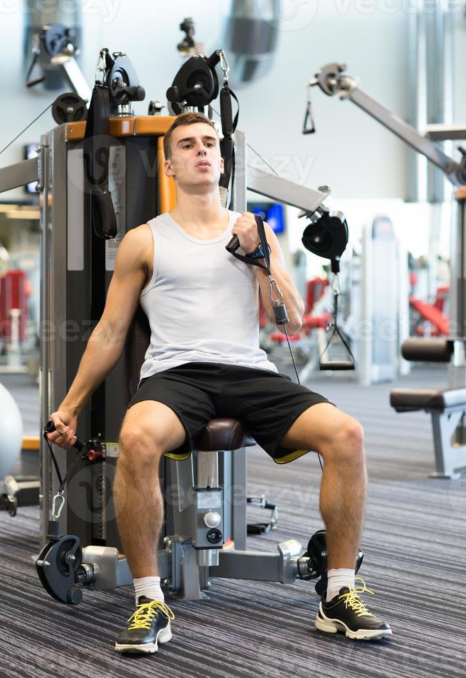 man exercising on gym machine photo