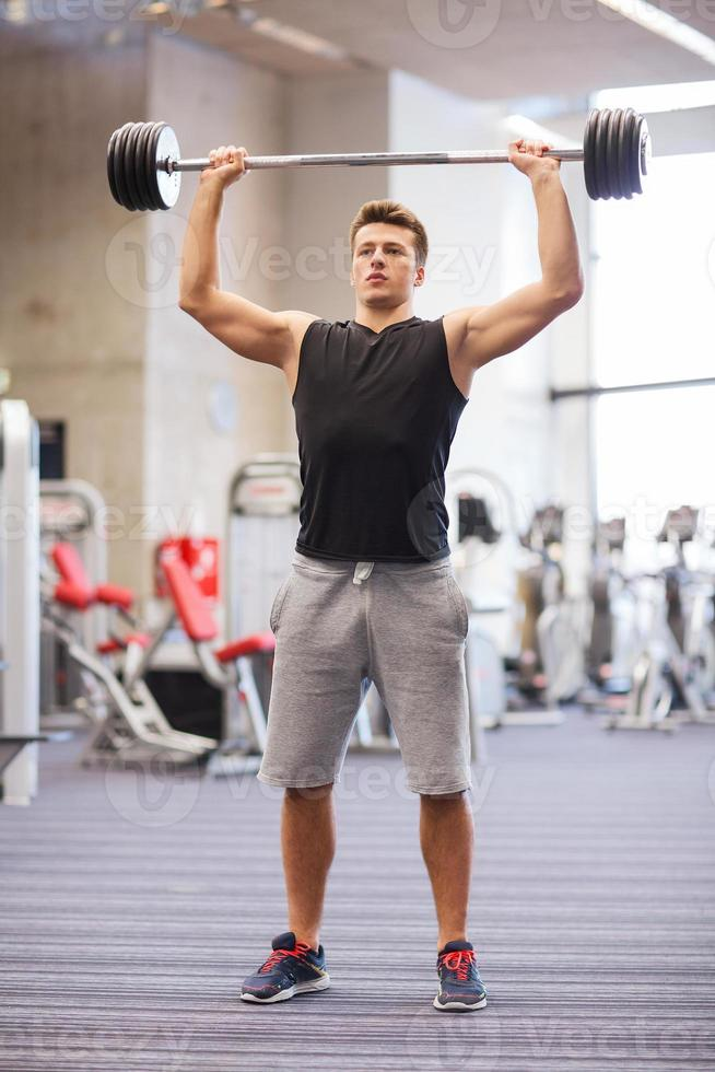 young man flexing muscles with barbell in gym photo
