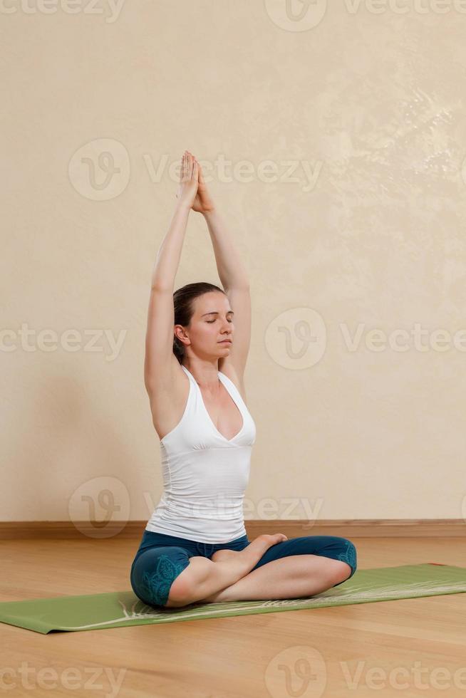 mujer caucásica está practicando yoga en el estudio (ardkhapadmasana) foto