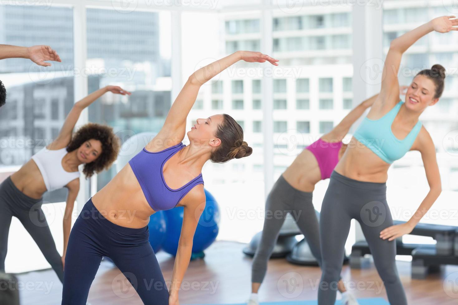 mujeres deportivas estirando las manos en clase de yoga foto