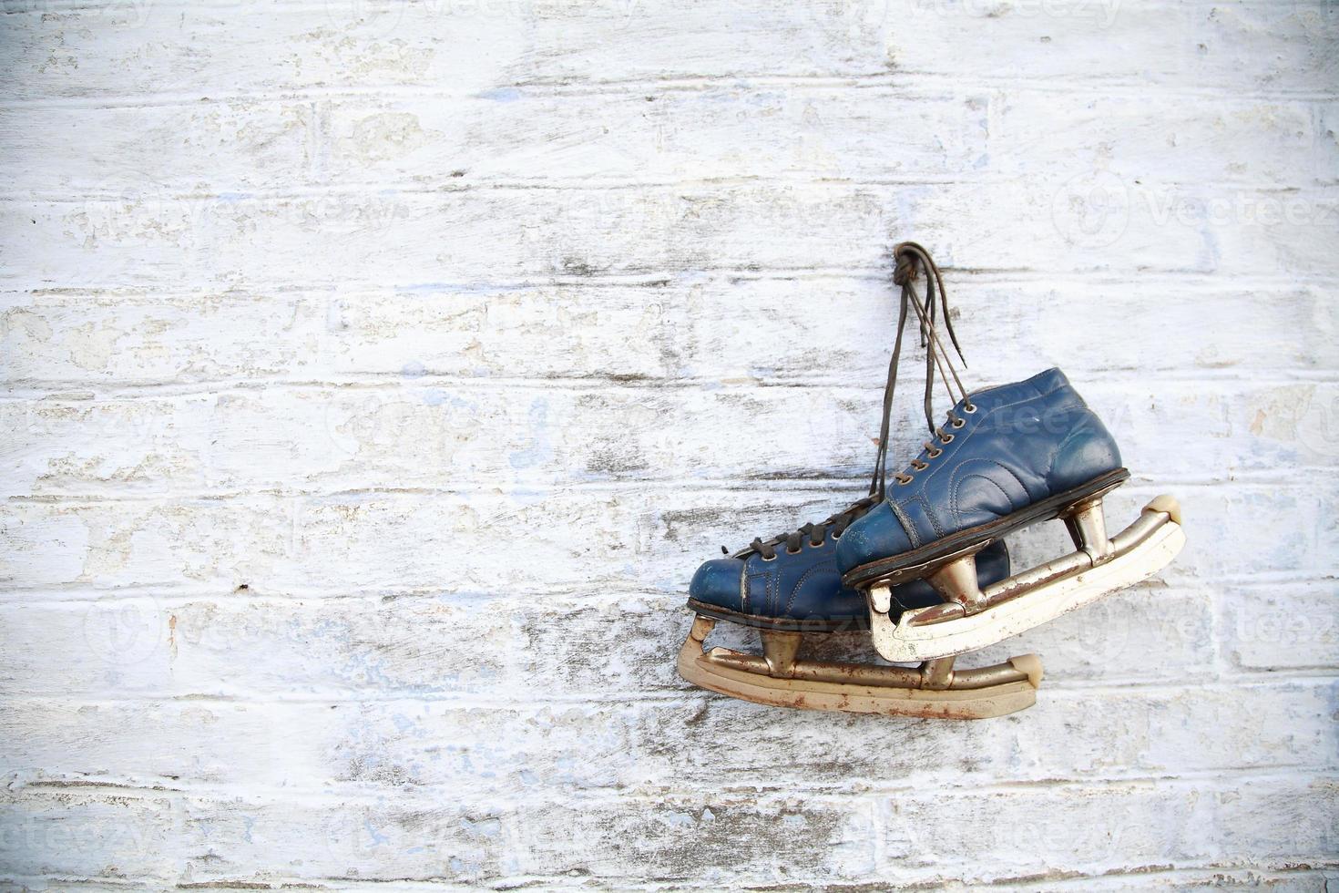 Women's ice skates hanging on wall photo