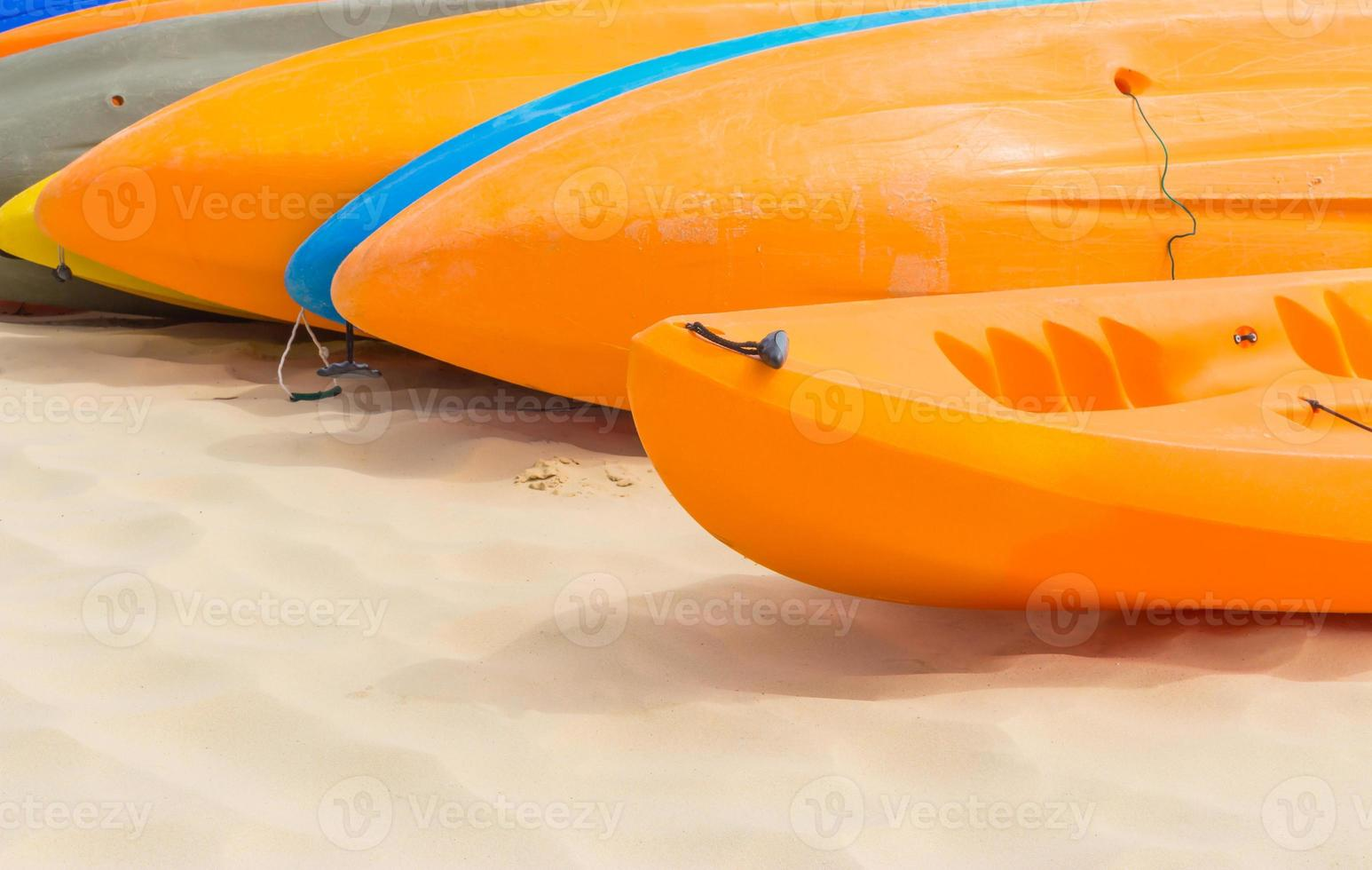 Colorful kayaks orderly dock on the beach photo