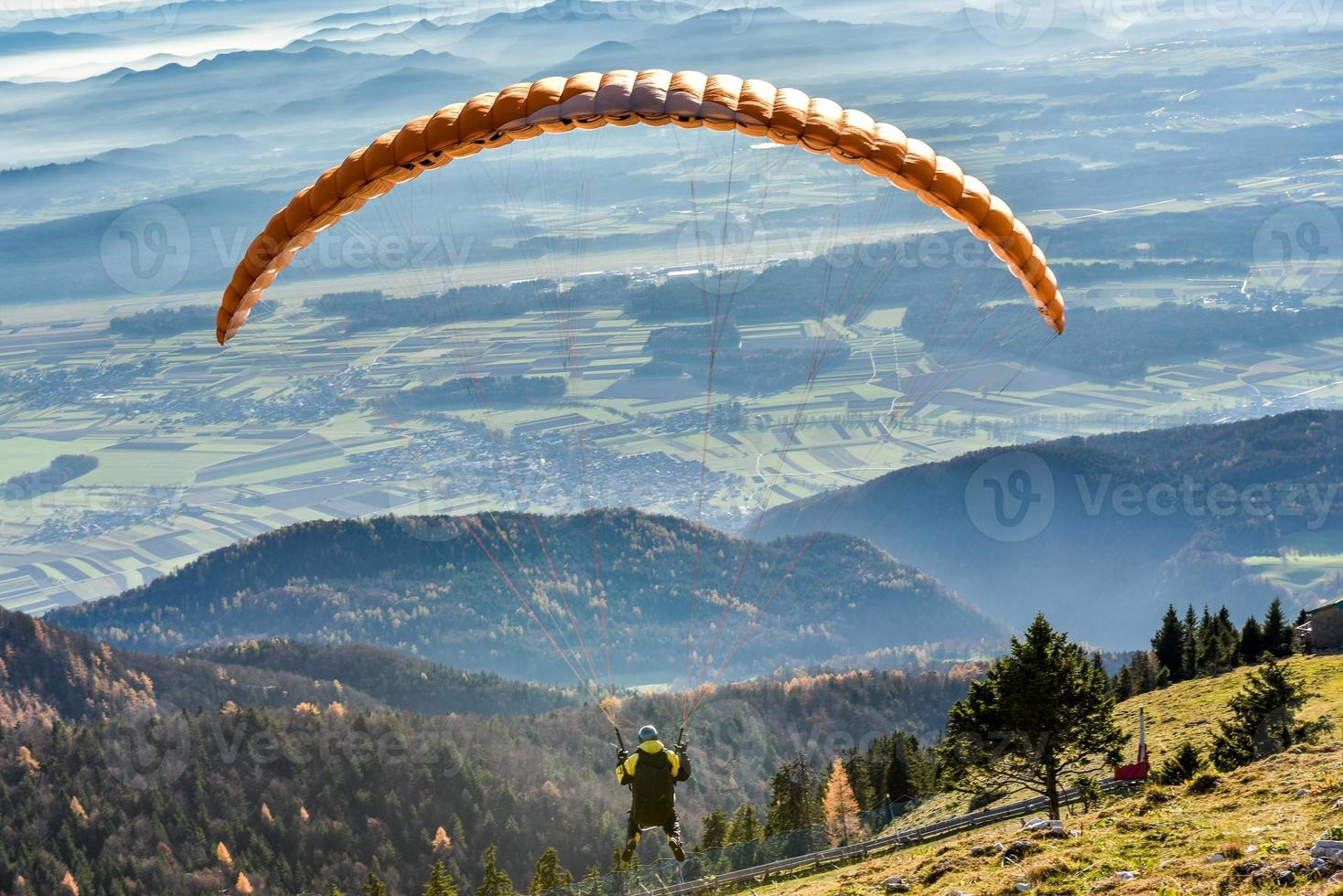 Paraglider is flying in the valley photo