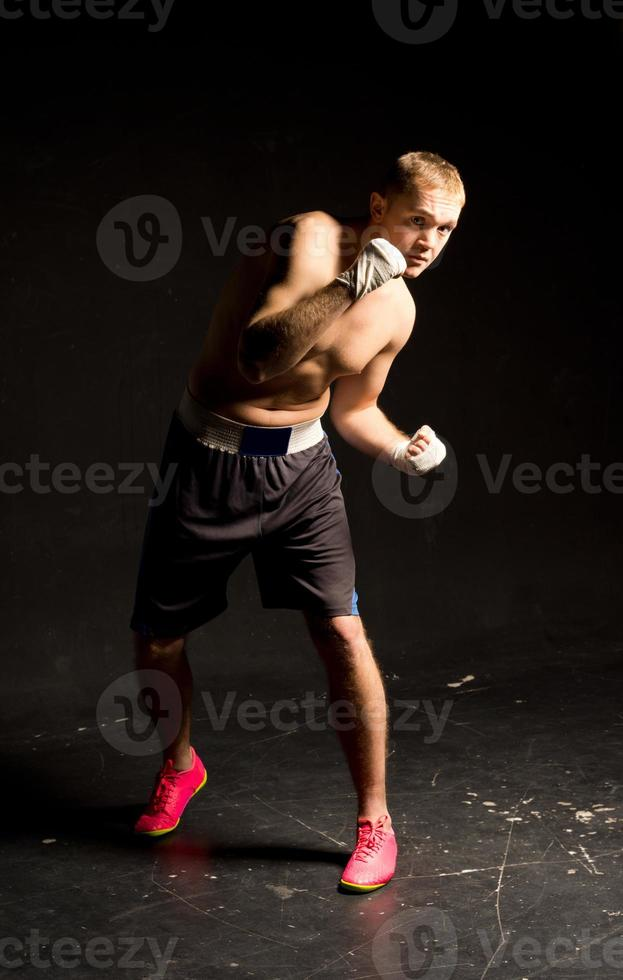 Agile young boxer moving around in the ring photo
